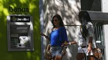 Two women walk past an ATM machine at Spain's k Bankia in Madrid on August 31, 2012. (JUAN MEDINA/REUTERS)