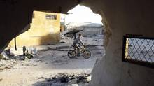A man cycles past a destroyed Syrian Army compound in Azaz, 47 kilometres north of Aleppo, on Friday. (Goran Tomasevic/REUTERS)