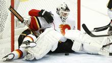 Calgary Flames goalie Miikka Kiprusoff guards the net after teammate Tom Kostopoulos fell behind him against the Colorado Avalanche during the third period of an NHL hockey game Sunday in Denver. (Barry Gutierrez/Associated Press)