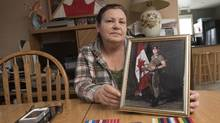 Canadian Forces veteran and Aboriginal Betty Ann Lavallee with her medals as she holds a photo of her son Trevor, a presently serving member of the Canadian Forces, in her home in Geary, N.B., on Nov. 5, 2016. (Stephen MacGillivray/THE CANADIAN PRESS)