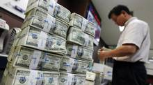 An employee of the Korea Exchange Bank counts money next to stacks of one hundred U.S. dollar banknotes at the bank's headquarters in Seoul, August 11, 2011. (Jo Yong-Hak/Reuters)