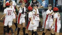 Teammates greet Canada's Noemie Marin (21), Caitlin Lever (9) and Melanie Matthews (12) in a softball game in the Beijing 2008 Olympics (Elaine Thompson/The Associated Press)