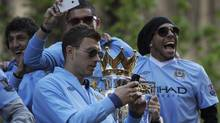 Manchester City's players parade the English Premier League trophy on a bus through the streets of Manchester, northern England May 14, 2012. REUTERS/Nigel Roddis (NIGEL RODDIS)