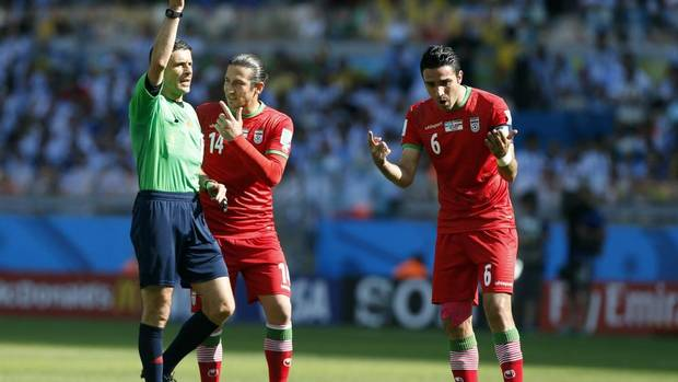 Referee Milorad Mazic from Serbia shows a yellow card to Iran's Javad Nekounam, right, during the group F World Cup soccer match between Argentina and Iran at the Mineirao Stadium in Belo Horizonte, Brazil. (Jon Super/AP)
