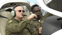Lt.-Gen. Charles Bouchard, sits in a cockpit of a DA40 Diamond Star as he listens to Lt. Chevon Smith, in this Dec. 7, 2006 photo in Montego Bay, Jamaica. (caporal-chef France Huard/DND)