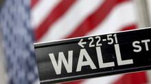 The Wall St. street sign is photographed in front of the American flag hanging on the New York Stock Exchange. (Mary Altaffer/AP)