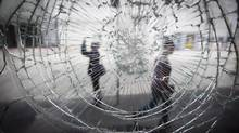 A danaged storefront window along Robson Street in Vancouver on June 23, 2011. (JOHN LEHMANN/THE GLOBE AND MAIL)