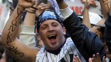 A New York Yankees fan cheers on his team with other fans Friday, Oct. 20, 2000, during a World Series rally in New York's Bryant Park. The Subway Series between the Yankee' and the New York Mets begins Saturday at Yankee Stadium. (AP Photo/Beth A. Keiser) (BETH A. KEISER)