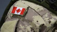 A Canadian flag sits on a member of the Canadian Armed Forces. The Forces have created a special team of investigators to handle sexual crimes. (Lars Hagberg/THE CANADIAN PRESS)