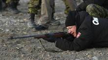 Canada's Prime Minister Stephen Harper shoots a .303 Lee-Enfield rifle while taking part in a demonstration by the Canadian Rangers at a camp near the Arctic community of Gjoa Haven, Nunavut August 20, 2013. (CHRIS WATTIE/REUTERS)