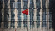 A Chinese national flag flutters at the headquarters of a commercial bank on a financial street near the headquarters of the People's Bank of China, China's central bank, in central Beijing in this November 24, 2014 file photo. (KIM KYUNG-HOON/REUTERS)