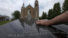 Ghislain Tanguay looks for his friend Richard Veilleux's name on a memorial dedicated to the victims of the tragedy, in Lac Megantic, Quebec July 5, 2015 (Christinne Muschi For The Globe and Mail)