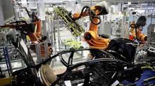A robot installs the glass roof on a car. (KAI PFAFFENBACH/REUTERS)