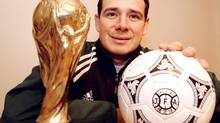 Winnipegger Hector Vergara poses with a replica of the World Cup trophy and a soccer ball from his personal collection on Monday Jan. 7, 2001 in Winnipeg. (Brian Donogh/CP)
