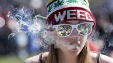 A woman smokes a joint during the annual 420 marijuana rally on Parliament Hill in 2016. (Justin Tang/The Canadian Press)