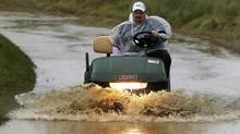 A golf cart makes it way through a flooded cart path as rain falls at Merion Country Club (Gene Puskar/AP)