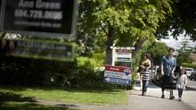 Potential buyers walk past real estate signs as they arrive an open house in the Kitsilano neighbourhood in Vancouver, British Columbia, Sunday, June 9, 2013. (Rafal Gerszak for The Globe and Mail)