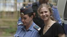 Maria Alekhina, foreground right, a member of feminist punk group Pussy Riot is escorted to a court room in Moscow, Tuesday, Aug. 7, 2012. (Alexander Zemlianichenko/AP)