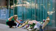 A woman places photographs at a memorial for Canadian actor Cory Monteith outside the Fairmont Pacific Rim Hotel in Vancouver on July 15, 2013. (DARRYL DYCK/THE CANADIAN PRESS)