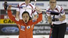 South Korea skip Ji-Sun Kim reacts to her shot as Canada's Jessica Mair and Laine Peters watch from behind during their game at the World Women's Curling Championships in Lethbridge, Alta. (ANDY CLARK/Reuters)