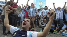 Argentina soccer fans celebrate after watching their side score a goal, via a live telecast of the World Cup group F match between Argentina and Nigeria, inside the FIFA Fan Fest area, in Porto Alegre, Brazil on June 25. (Nabor Goulart/AP)