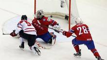 Canada's Mark Scheifele (L) scores past Norway's goalie Steffen Soberg (C) and Niklas Roest (R) during the second period of their men's ice hockey World Championship Group A game at Chizhovka Arena in Minsk May 20, 2014. (VASILY FEDOSENKO/REUTERS)