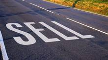 view of a sign painted on the surface of the road saying sell (Stockbyte/Getty Images)