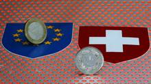 One Euro and one Swiss Franc coins are seen in Zurich in this file photo. (Reuters)