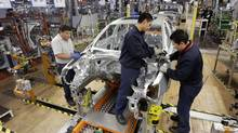 Employees work on the assembly line at the Volkswagen factory in Puebla in this 2010 file photo. Mexico has become the preferred centre of manufacturing for multinational companies looking to supply the Americas and, increasingly, beyond. (STR/REUTERS)
