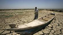 An Iraqi man walks past a canoe siting on dry, cracked earth in the Chibayish marshes near the southern Iraqi city of Nasiriyah. Marsh areas in southern Iraq have been affected since the Islamic State group started closing the gates of a dam on the Euphrates River in the central city of Ramadi, which is under the jihadist group's control. (Haidar Hamdani/AFP/Getty Images)