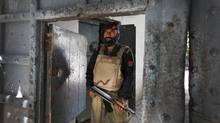 A police officer stands guard May 8, 2011, at the gates of Abbottabad's central police station, where officials announced recently that foreign guests cannot stay in hotels without written permission and should remain off the streets at night. (Charla Jones for The Globe and Mail)