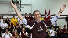 Liberal Leader Michael Ignatieff salutes the crowd after slipping on a team jersey during a town hall meeting with high school students in Sault Ste Marie, Ont. (Paul Chiasson/The Canadian Press)