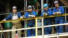 Workers at Suncor's Fort McMurray oil sands processing plant take a break during construction work in this file photo. (JEFF McINTOS/GLOBE AND MAIL)