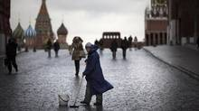 A street worker cleans paving stones in Red Square with St. Basil's Cathedral, left, Lenin Mausoleum, center, and the Spasskaya Tower, right, in Moscow, Russia, on December 22, 2015. (Alexander Zemlianichenko/AP)