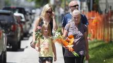 A family carries flowers into Sainte-Agnes Church in the town of Lac Megantic, Quebec July 12, 2013. Police erected an 8-foot (2.5-meter) fence blocking from view what was once a downtown core of restaurants, bars and shops - but which now resembles a blackened warzone after a train pulling 72 cars of crude oil jumped the track and exploded into flames in Lac Megantic on July 6. Some 24 bodies have so far been recovered in the blast zone, police said on Thursday, with another 26 reported missing and presumed dead. (Christinne Muschi/REUTERS)