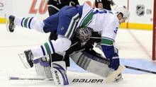 Vancouver Canucks center Henrik Sedin, top, of Sweden falls over Los Angeles Kings goalie Jonathan Quick during the first period in Game 3 of a first-round NHL hockey Western Conference playoff series, Monday, April 19, 2010, in Los Angeles. ( (Mark J. Terrill/AP)