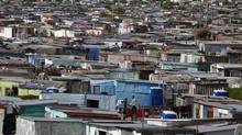 Residents walk through shacks in Cape Town's crime-ridden Khayelitsha township in this picture taken July 9, 2012. At least 11 people have died at the hands of vigilantes in the township since January as angry residents, tired of poor policing, take the law into their own hands. Picture taken July 9, 2012. (Mike Hutchings/REUTERS)