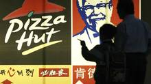 People stand in front of a poster of KFC and Pizza Hut in Guangzhou, capital of south China's Guangdong province in this file photo. (JOE TAN/REUTERS)