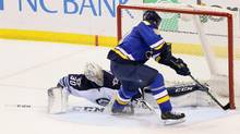 Winnipeg Jets goaltender Connor Hellebuyck, left, makes a leg save on a shot by St. Louis Blues right wing Vladimir Tarasenko in a shootout during an NHL hockey game Tuesday, Feb. 9, 2016, in St. Louis. (Chris Lee/AP)