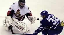 Ottawa Senators goalie Robin Lehner (L) knocks the puck away from Toronto Maple Leafs forward Kris Versteeg (R) during the first period of their NHL pre-season hockey game in Toronto September 21, 2010. (MIKE CASSESE)