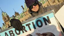 A protester waves anti-abortion placards on Parliament Hill in 2006. (Bill Grimshaw/Bill Grimshaw for The Globe and Mail)