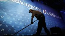 A janitor mops the stage in preparation for Prime Minister Stephen Harper's speech later in the day at the Conservative convention in Calgary, Friday, Nov. 1, 2013. (Jeff McIntosh/THE CANADIAN PRESS)