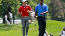 Rory McIlroy (L) of Northern Ireland talks with Tiger Woods of the U.S. as they approach the first green during round one of the BMW Championship golf tournament in Carmel, Indiana September 6, 2012. (BRENT SMITH/Reuters)