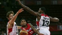 Puerto Rico's Elias Ayuso, center, drives past Canada's Aaron Doornekamp, left, and Tristan Thompson, to shoot during a FIBA World Cup qualifying basketball game in Caracas, Venezuela, Saturday, Aug. 31, 2013. Puerto Rico defeated Canada 83-67. (Juan Carlos Solorzano/AP)