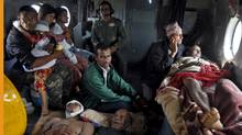 Victims of Saturday's earthquake rest inside an Indian Air Force helicopter as they are evacuated from Trishuli Bazar to the airport in Kathmandu, Nepal, April 27, 2015. TPX IMAGES OF THE DAY (Jitendra Prakash/REUTERS)