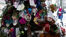 Portraits of slain students and teachers hang from a tree at a memorial inNewtown, Conn. Tuesday, Dec. 25, 2012. People continue to visit memorials in the wake of the shootings after gunman Adam Lanza walked into Sandy Hook Elementary School inNewtown, Conn., Dec. 14, and opened fire, killing 26, including 20 children, before killing himself. (Craig Ruttle/AP Photo)