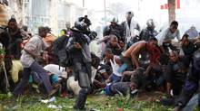 Riot police chase opposition UDPS supporters caught in a cloud of tear gas outside N'Djili airport in Democratic Republic of Congo's capital Kinshasa November 26, 2011. (Finbarr O'Reilly/Reuters)