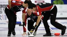 Ontario skip Glenn Howard, centre, watches his shot as second Brent Laing, left, and lead Craig Savill sweep during a morning draw against British Columbia at the Tim Hortons Brier in Saskatoon, March, 7, 2012. (Jonathan Hayward/The Canadian Press/Jonathan Hayward/The Canadian Press)