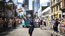 A Toronto Police Service parking-enforcement officer waves a Pride flag during the Pride Parade in 2016 (Mark Blinc/THE CANADIAN PRES)