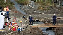 Search and Rescue personnel continue the search for bodies buried in mud at the landslide in Oso, Wash., Wednesday, April 9, 2014. (Thomas Boyd/AP)